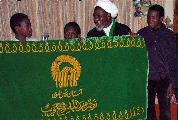 اهداء رایة حرم الامام الرضا(ع) للشیخ الزکزاکي داخل زنزانته فی نیجیریا