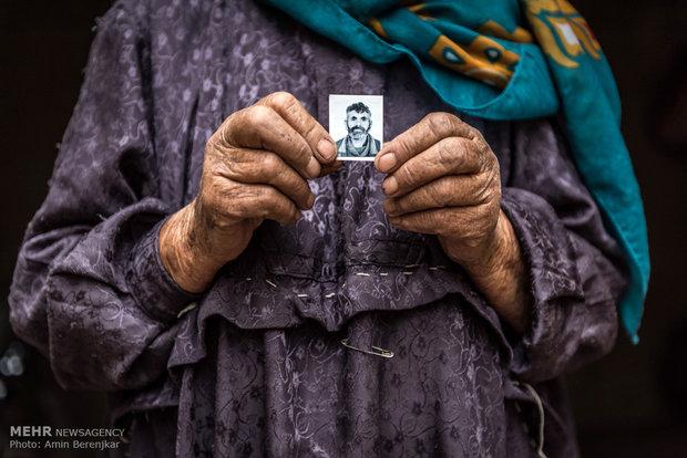گلبگم نوری، ساکن روستای داشگسن، عکس یکی از پسران خود را نشان می دهند که یک سال است برای کار به تهران رفته است و بعلت مشغله و درگیری زندگی با آنها تماس نداشته است.