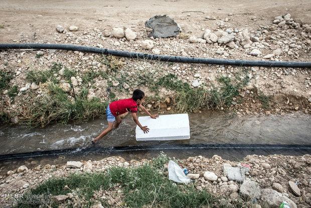 روستای کویج، یکی از کودکان روستا درحال موج سواری با تکه ای از کائوچو بر روی آب روان است. بسیاری از کودکان از امکانات اولیه سرگرمی و برنامه های فرهنگی محروم هستند.