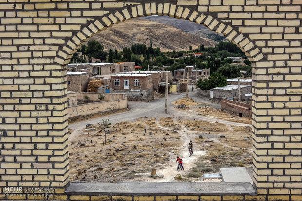 کودکان روستای کویج در حال بازی در کنار ساختمان درحال تکمیل نزدیک قبرستان این روستا هستند.