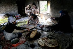 Iranian women bake loaves of flatbread
