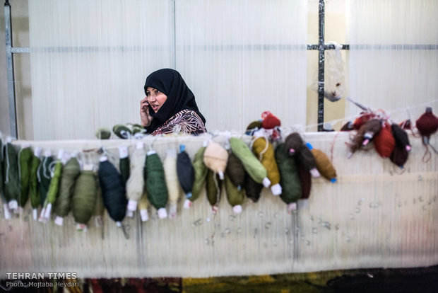 Hosseini is talking on the phone with one of her trainees in the carpet weaving workshop.