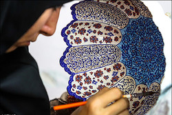 An Iranian artisan forms an inlaid enamel bowl in an undated photo