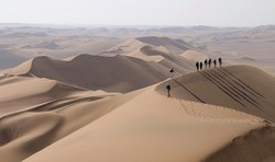 A group traverse the mega dunes on the eastern flank of the Lut Desert in Iran. (Photo credit: Jerome Poulin/Secret Compass)