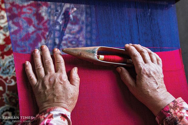 A woman is weaving a silk cloth.