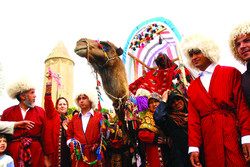 Turkmen nomads take part in a wedding ceremony in northern Iran. The upper part of Gonbad-e Qabus, a UNESCO-inscribed tower, is seen in the foreground.
