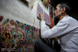 A man stares at an intricate carpet pattern installed atop a traditional loom while weaving a silk carpet in the historical city of Tabriz, April 2, 2017.