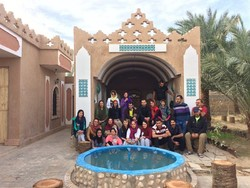 A cluster of domestic and international tourists pose for a photo while visiting an Iranian eco-lodge in central Iran.