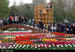 Visitors admire beauty of the vibrant, multi-colored flowers during a tulips festival at Chamran Park in Karaj on April 15, 2017.