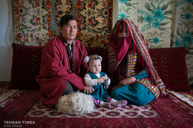 A newly-wed Turkmen couple pose for a photo with a little child. They believe that cuddling a little child during the wedding ceremony would lead to their childbearing.