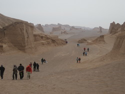 An undated photo depicts travelers walking across the scenic Shahdad Desert in Kerman province.