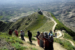 A cluster of pilgrims walk in a scenic mountainous route that leads to the shrine of Khalid Nabi in Golestan province near the border with Turkmenistan, April 29, 2017.