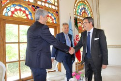 Iranian tourism official Mohammadreza Pouyandeh (L) shakes hands with Spanish Paradores official Juan Carlos Sanchez Gavez in Tehran on May 1, 2017. Spanish Ambassador Eduardo Lopez Busquets is seen i