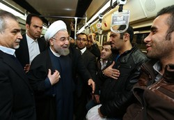 Hassan Rouhani talks with commuters in a subway in Tehran to encourage people to use public transport to control air pollution