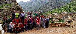 Travelers pose for a photo with a picturesque landscape of Iran's Kurdistan province in the background.