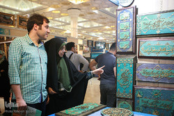 People look at handcrafted calligraphy panels at the 25th International Holy Quran Exhibition in Tehran, June 4, 2017.