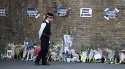A police officer stands in front of messages and tributes June 19 left near where a man died and 10 people were injured after a van was rammed into a crowd of worshippers near a mosque in north London