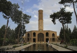 Photo depicts people visiting Bagh-e Dolat Abad, a richly manicured historical garden in Yazd, central Iran, on July 10, 2017. An octagonal pavilion surmounted by an imposing wind tower is seen in the