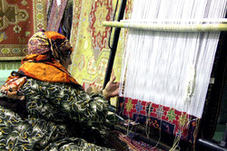 An Iranian nomad weaves a rug in an undated photo.