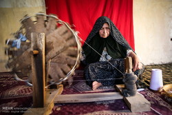 A woman uses an indigenous spinning wheel to make thread from natural fiber at a small-scale workshop in Ruin, a village in northeast Iran, August 5, 2107.