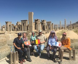 Foreign travelers pose for a photo during their visit to Persepolis, southern Iran.