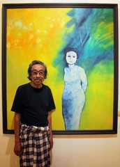 Indonesian painter Jeihan Sukmantoro poses with one his works in an undated photo.