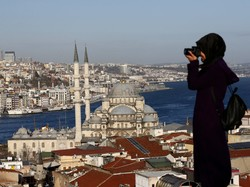 A woman takes photographs in front of the New Mosque by the Bosporus strait in Istanbul, Turkey, January 12, 2016. (Reuters/Murad Sezer)