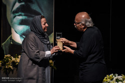 Director Alireza Davudnejad (R) receives his award from his fellow filmmaker Marzieh Borumand during the Davud Rashidi Awards at Tehran's City Theater Complex on August 26, 2017. (Mehr/Behnam Tofiqi)