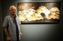 Akbar Nemati poses beside one of hisartworks on display in an exhibition at Tehran's E1 Gallery on August 25, 2017.
