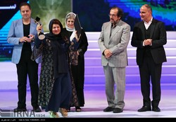 """Director Puran Derkhshandeh accepts the award for best film for her drama """"Under the Smoky Roof"""" during the 2nd Health Film Festival in Tehran at Vahdat Hall on August 27, 2017. Jury members are also"""