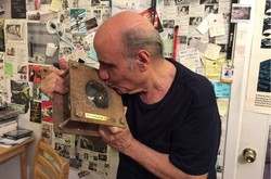 Iranian director Amir Naderi plants a kiss on an award he received for his lifetime achievement from the ISFA at his office in New York. (Photo by ISFA)