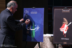 """Vocalist Ali-Asghar Shahzeidi signs a poster for """"The Honored"""" after the unveiling of the album at the Art Bureau in Tehran on September 25, 2017. (Mehr/Mohammad Moheimani)"""