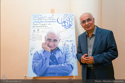 Writer Hushang Moradi Kermani poses beside his picture signed by a number of officials and artists during his 72nd birthday celebration at the Imam Ali (AS) Religious Arts Museum on September 10, 2016