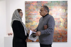 Mojdeh Gallery manager Mojdeh Tabatabai (L) and filmmaker Masud Forutan talk together in an exhibition of calligraphic paintings by Mohsen Karami at the gallery on October 27, 2017. (Iranart.ir)
