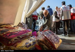 An old man is donating a blanket to the earthquake-stricken victims of Kermanshah.