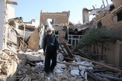 An old man is standing on the ruins of his house devastated by the powerful quake in Kermanshah.