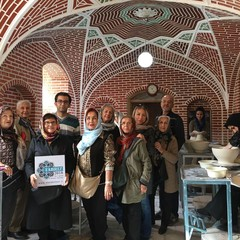 International and domestic travelers pose for a photo during visit to a traditional pottery workshop in Tabriz, northeast Iran, while one of them is flashing a logo for the Tabriz 2018 event.