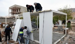 A group of construction workers are building a Conex box as a temporary shelter in Sarpol-e Zahab, Kermanshah province. (Photo by Abdollah Moradi/ IRIB)