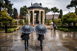 Two girls are walking towards Tomb of Hafez in Shiraz on a rainy day in February 2017.