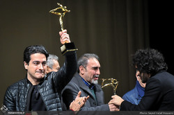 "Vocalist Homayun Shajarian (L) and composer Sohrab Purnazeri (R) accept awards for their album ""Subdued"" during the House of Music Celebration at Tehran's Vahdat Hall on December 12, 2017. (Honaronlin"