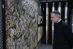 "British Museum director Hartwig Fischer glances at Jackson Pollock's ""Mural on Indian Red Ground"" in the storehouse of the Tehran Museum of Contemporary Art on December 23, 2017. (TMCA)"