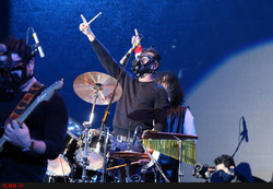 Members of Iranian rocker Kaveh Afaq's band dressed in gas masks perform at Tehran's Milad Tower on December 31, 2017 to remember the victims of Iraq's chemical attack on the Iranian town of Sardasht