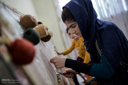 A photo of a young girl who is weaving a carpet (Tehran Times/Mojtaba Heidari)