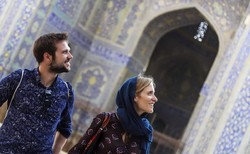 Foreign nationals look at blue-tiled mosaics of Imam Mosque, a Safavid-era monument in Isfahan, central Iran.