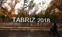 "A couple passes by an official logo that reads ""Tabriz 2018"" which refers to the selection of northwestern Iranian city as the capital of Islamic tourism in 2018."