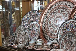 A shop window displays handcrafted metalwork by Iranian artisans