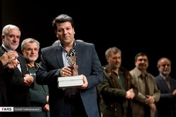 """Damascus Time"" producer Mohammad Khazaei accepts an award on behalf of director Ebrahim Hatamikia during the 7th Qoqnus Screen Awards at Andisheh Hall in Tehran on February 16, 2018. (Fars/Soheil Sah"