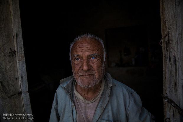 پیرمرد ساکن روستایی دورافتاده، در آستانهی در ورودی خانه با چشمان بیمار ایستاده است. او قادر به کار کردن نیست و بخش زیادی از بینایی خود را در اثر کمبود امکانات بهداشتی و درمانی از دست داده است.
