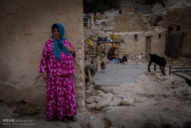 زنی که بز خانواده را برای خوردن گیاهان به روستا آورده، کنار دیوار خانهای خالی از سکنه ایستاده است. تلفات دام و در نتیجه از بین رفتن منبع درآمد خانوادهها از دلایل مهاجرت به شهر برای یافتن شغل و منبع درآمد جدید است.