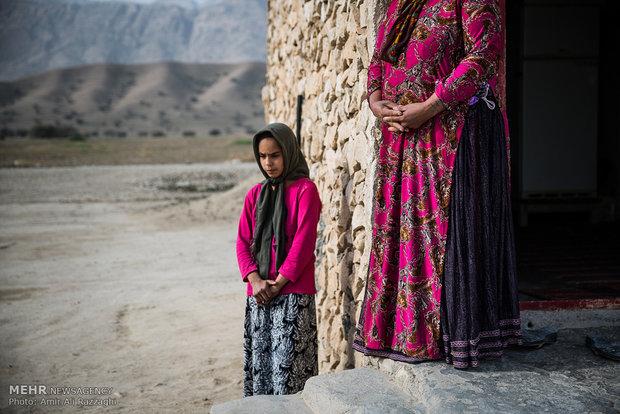 دختر خردسالی از روستای تنگخون در کنار مادر به دوردست روستا نگاه میکند. بیشتر دختران روستا تا مقطع ششم ابتدایی قادر به تحصیل هستند و برای ادامه تحصیل با پرداخت هزینههایی خارج از توان مالی خانواده راهی شهرهای اطراف میشوند.